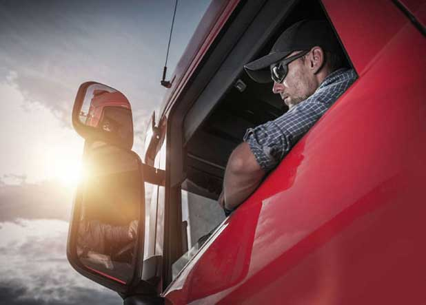 Truck driver looking at his side mirror inside his red truck