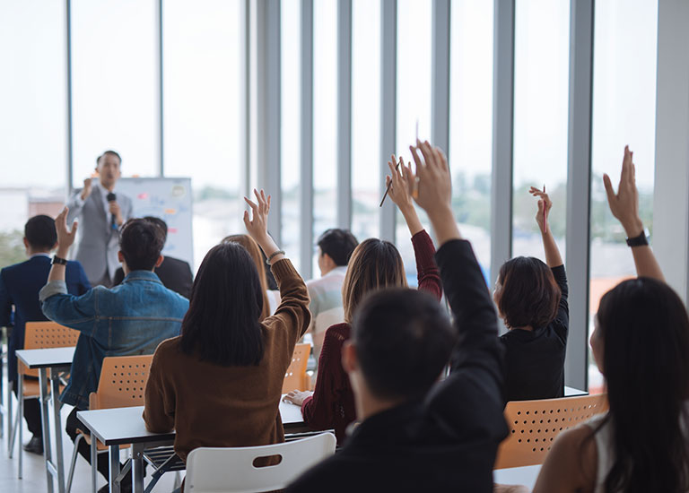 Student raises hand to answer inside the classroom